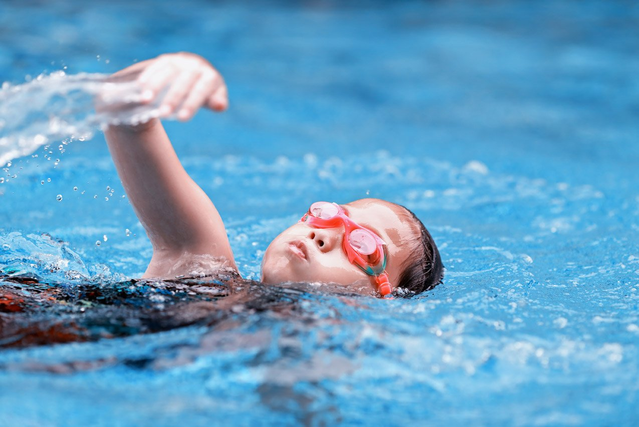 Маленький ребенок плывет в бассейне кролем