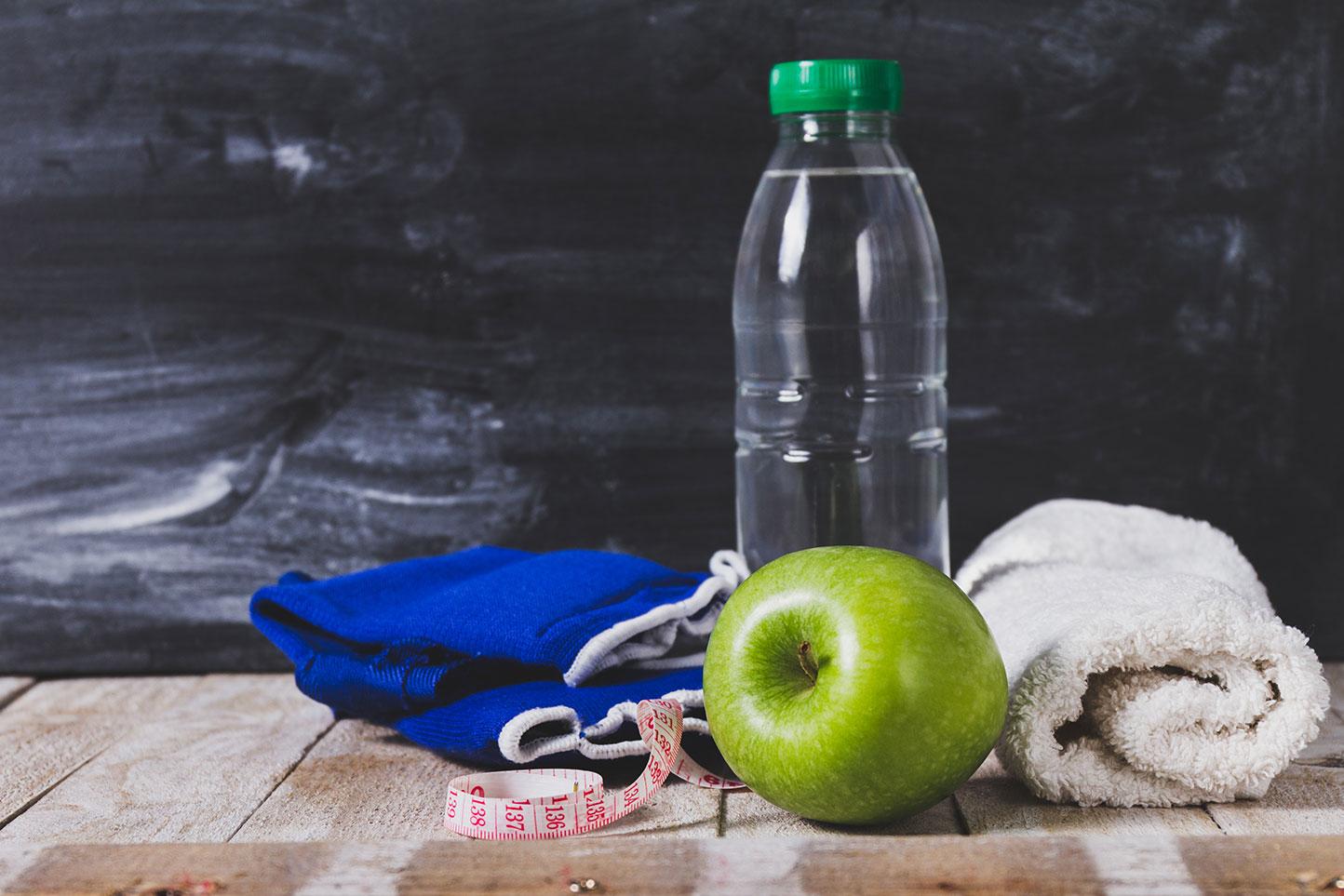 Голубое полотенце, бутылка чистой воды, яблоко, сантиметровая лента