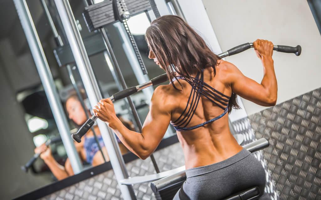 Спортивная девушка в тренажерном зале, выполняет вертикальную тягу блока для широчайших мышц спины