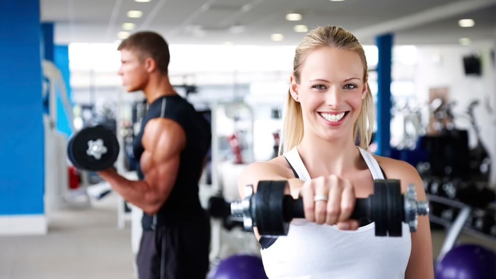 Парень и девушка поднимают гантели в тренажерном зале